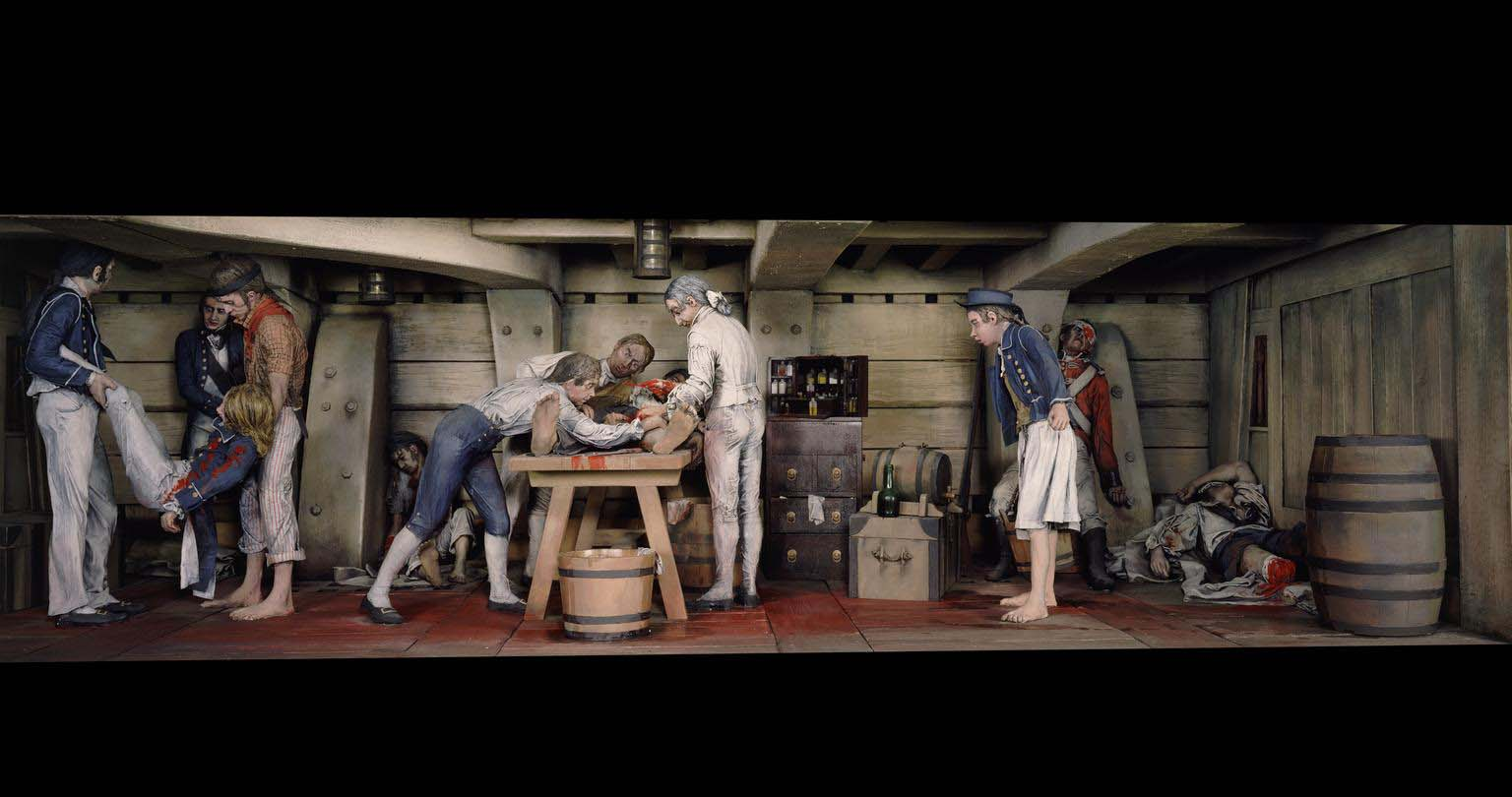 a photo of a diorama showing a ship's deck with sailors being carried and operated on