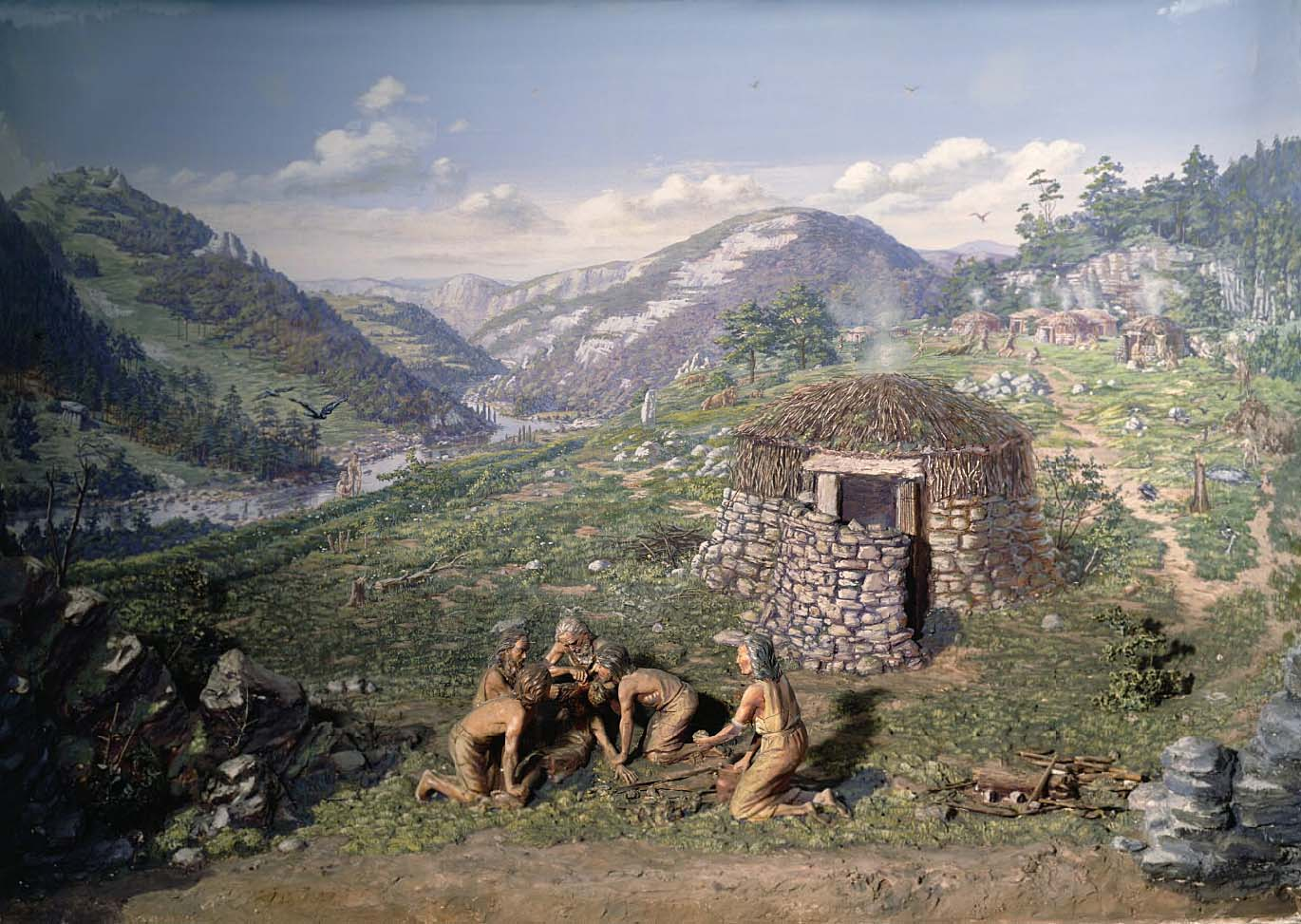 a model of a group of people performing on operation outside a small stone roundhouse
