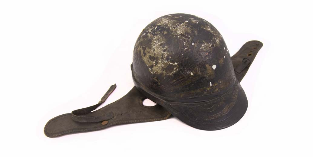 a photo of an old motorcycle helmet with leather straps