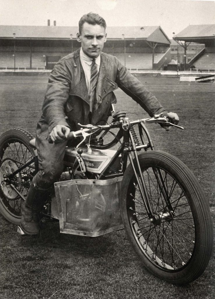 a black and white photo of a man on a motorcycle