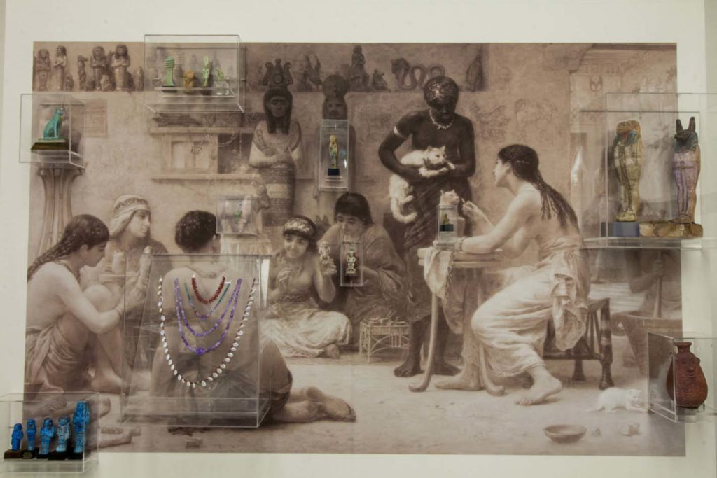 a photo of a large scale painting showing an Ancient Egyptian scene with artefacts mounted on it