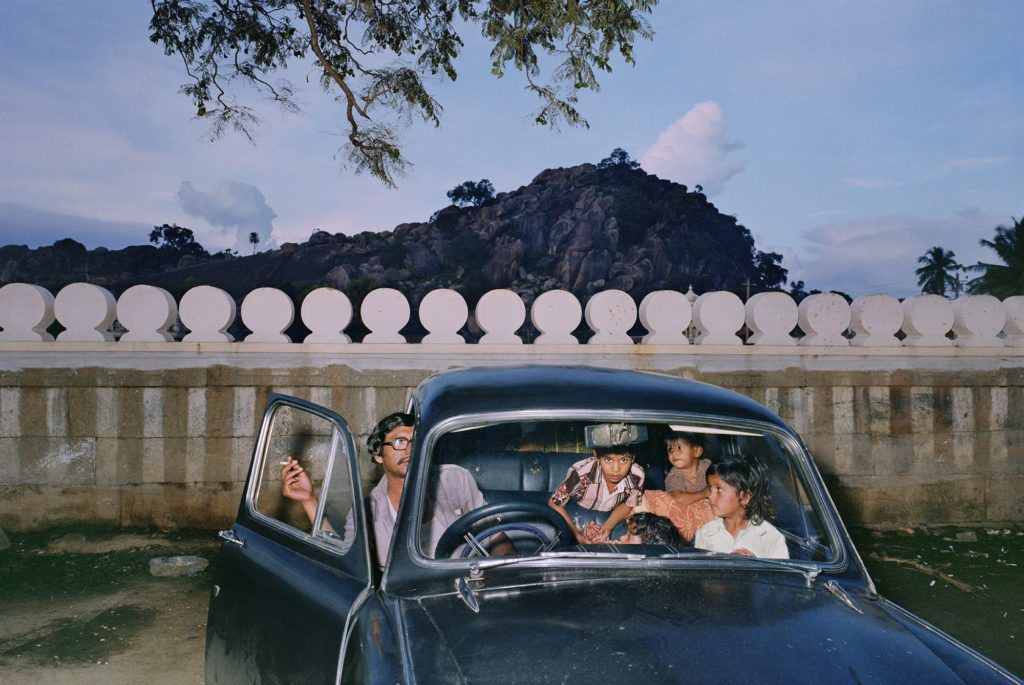 photogrpah of Indian man and four children inside black car, the driver's door is open and the man is holding a cigarette