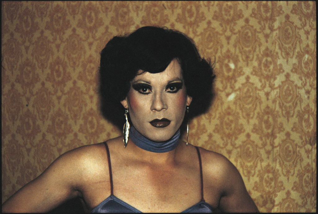 colour photograph showing head and shoulders portrait of trans male in evening wear and full makeup