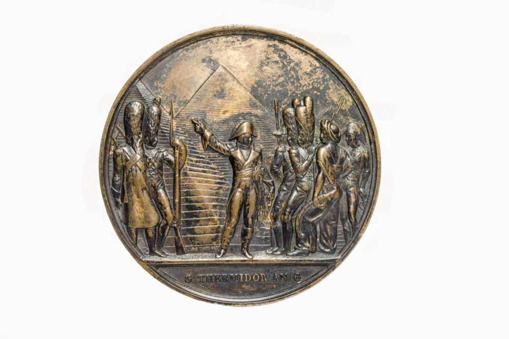 a photo of a coin with an image of Napoleon and his soldiers in front of the pyramids