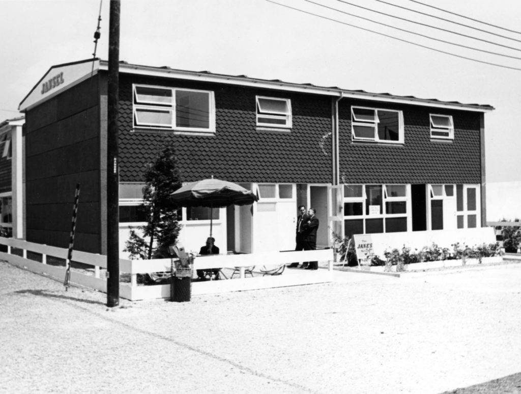 monochrome photograph showing man sat at table in the patio area of a row of prefab homes