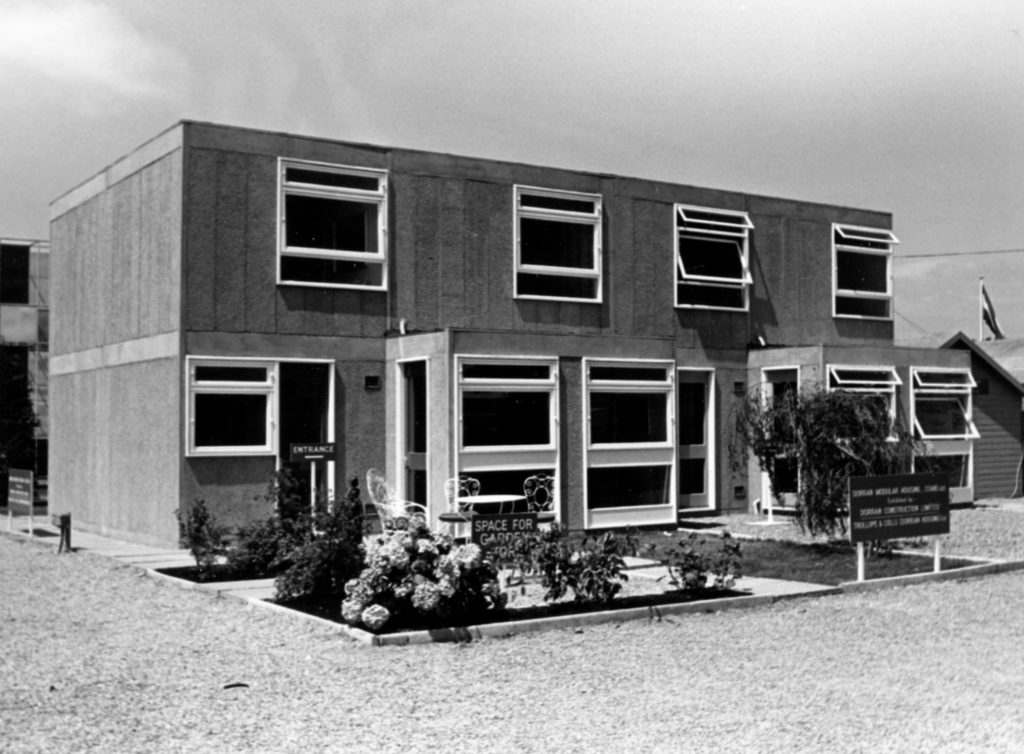 monochrome photograph of semi-detached housing block with garden and seating outside