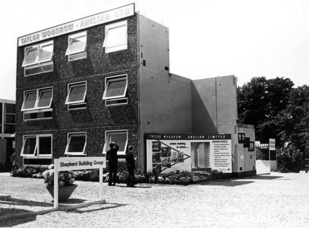 monochrome photograph showing two men in suits looking at prefab building