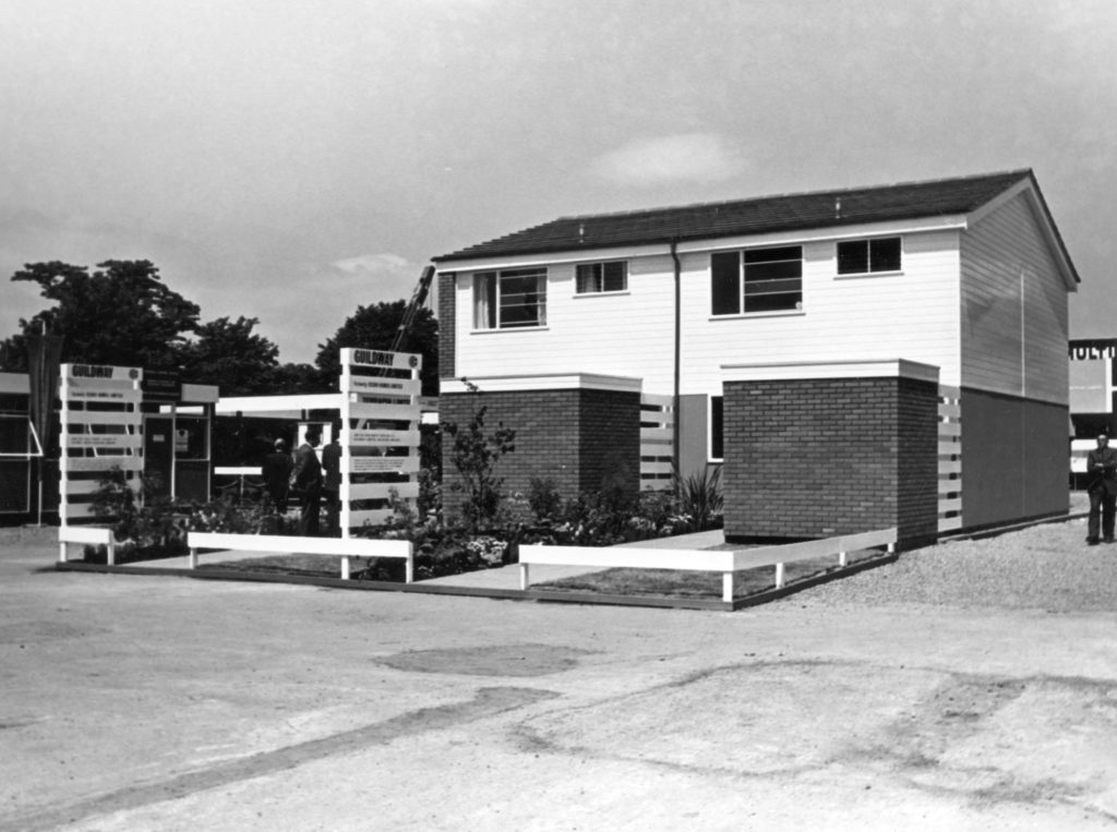 Black and white photograph showing the exterior of a prefabricated semi-detached home