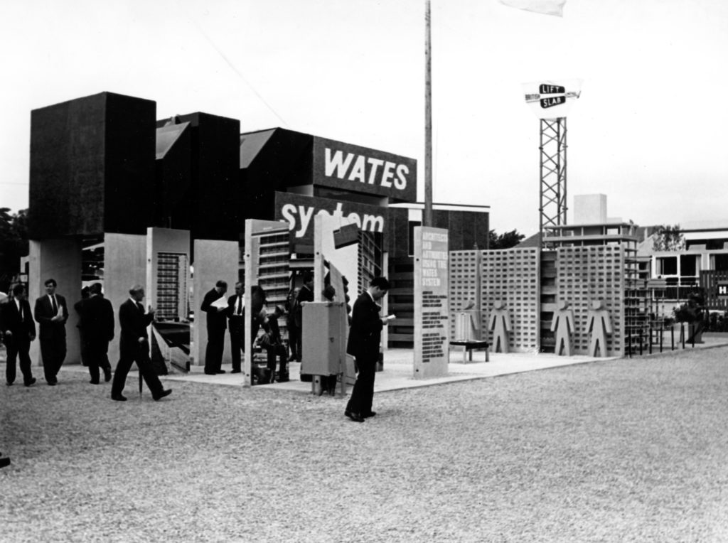 monochrome photograph showing a group of people conversing and reading around a large display advertising for WATES System