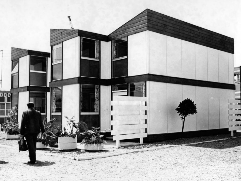 monochrome photograph showing man in suit walking past a row of two-storey prefab homes