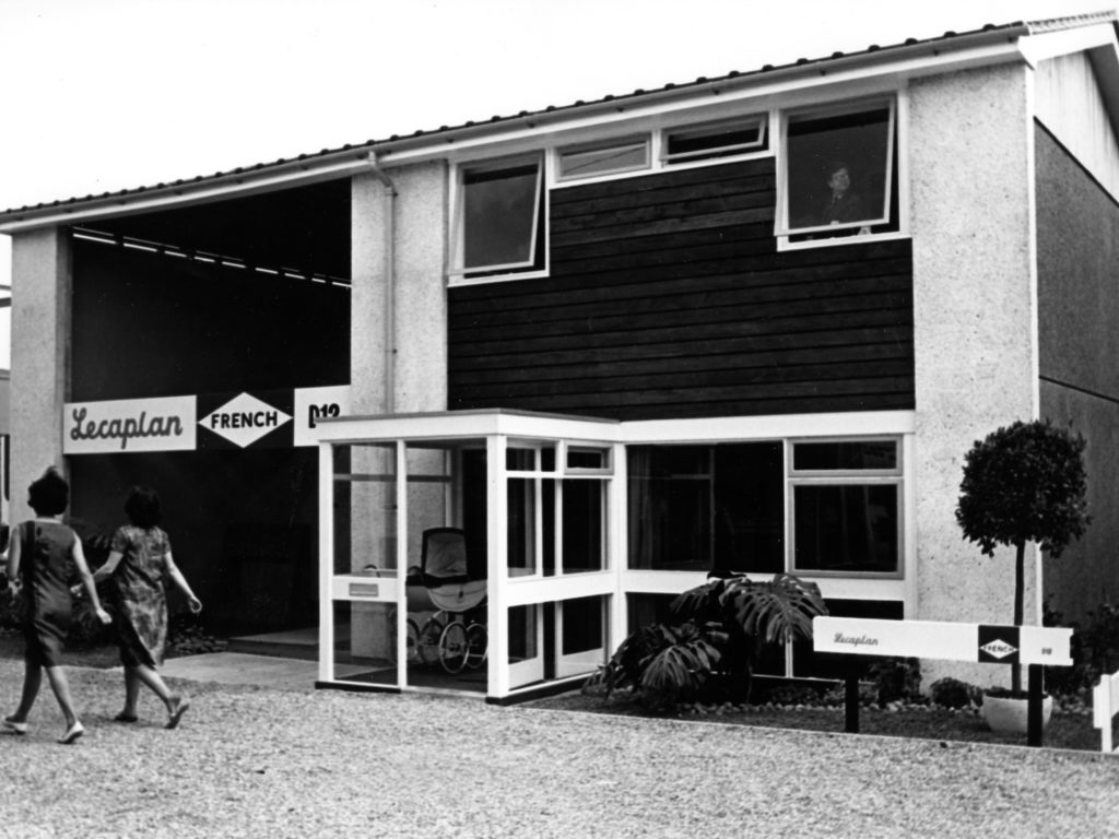 monochrome photograph of two women in 60s style dresses walking past a prefab building with sign reading 'lecaplan'