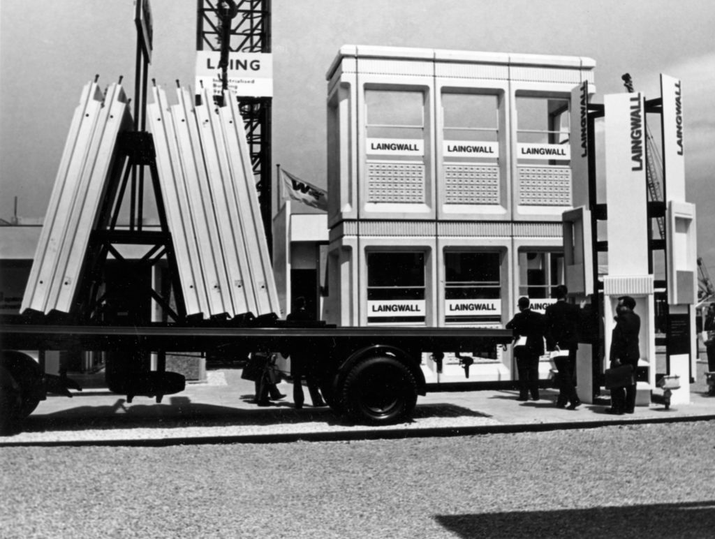 monochrome photograph showing lorry carrying components for a prefab building, which is under construction in the background