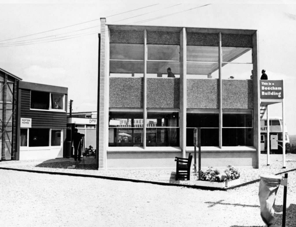 monochrome photograph showing prefab building with large windows, with sign reading 'this is a beecham building'