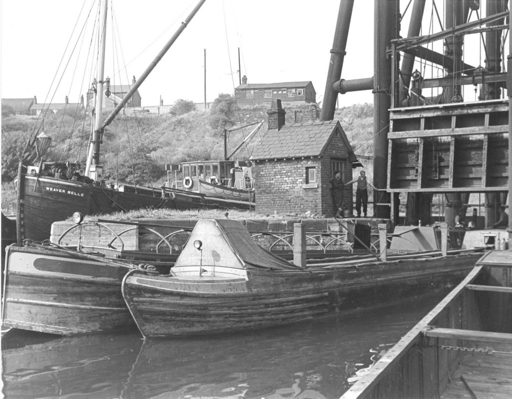 a photo of two canal boats moored next to a crane and other canal side buildings