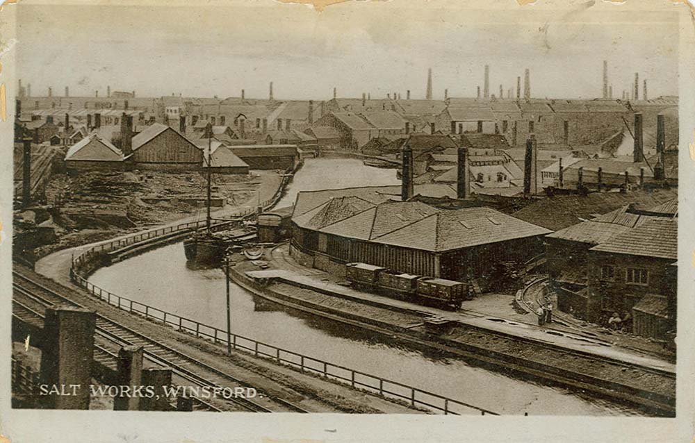 a postcard showing an industrial complex with a river running through it