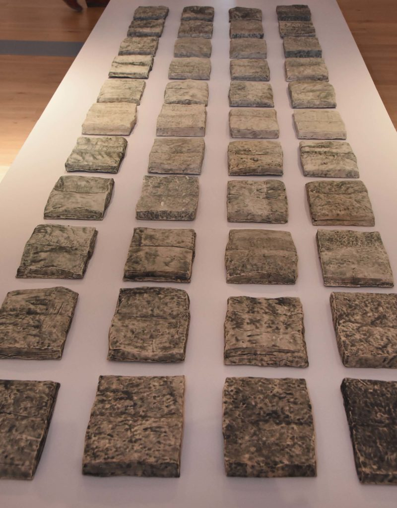 a photo of a series of clay book-like slabs made by Sara Radstone laid out on a plinth in a gallery