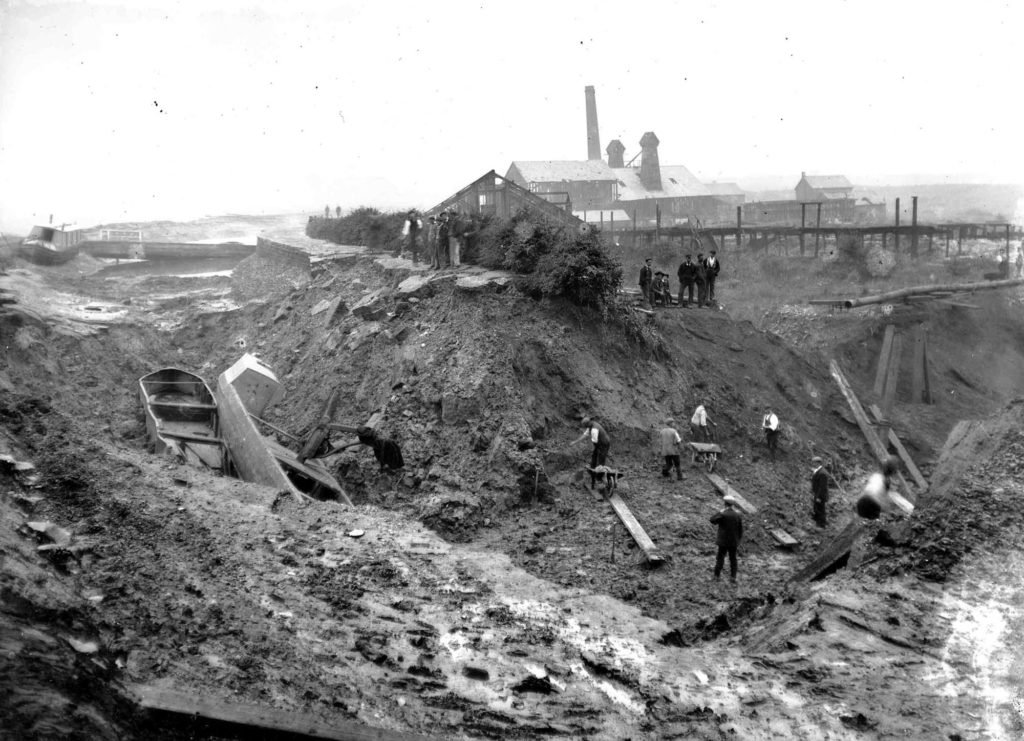 a black and whiyte photo of subsided earthworks and stranded boats with men and wheelbarrows