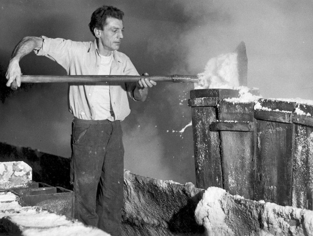 a photo of a man lifting a shovel full of salt out of a wooden cart