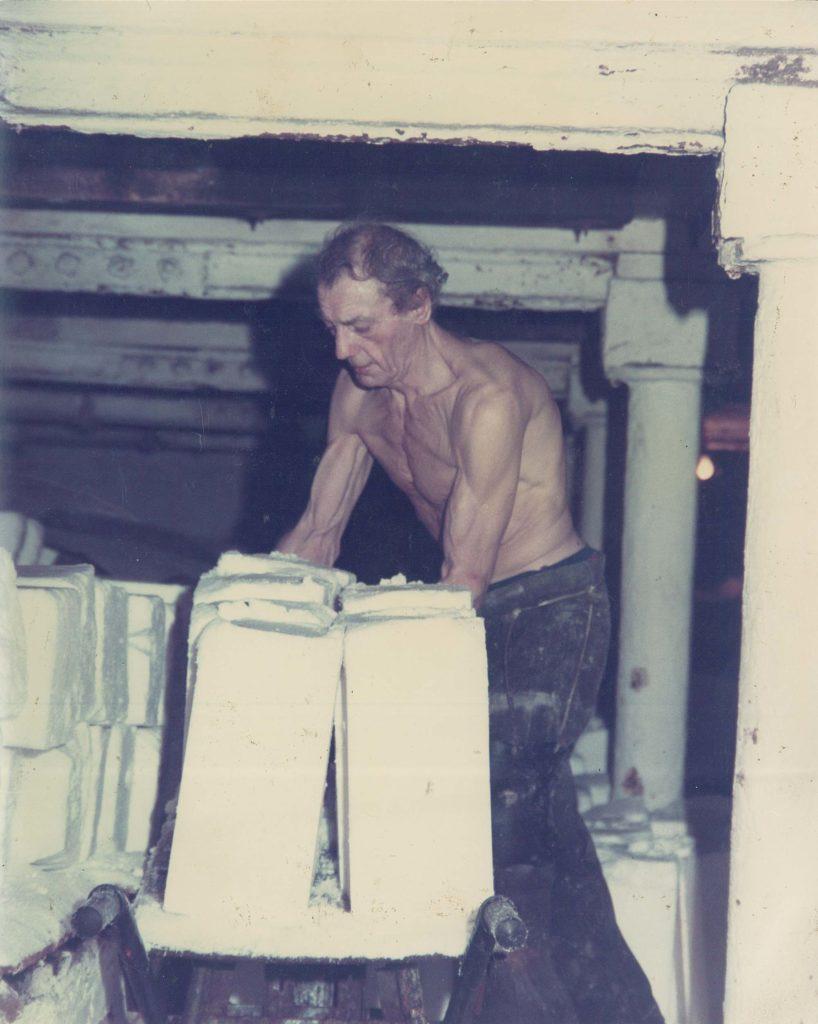 a colour photo of a man loading blocks of slat onto a trolley