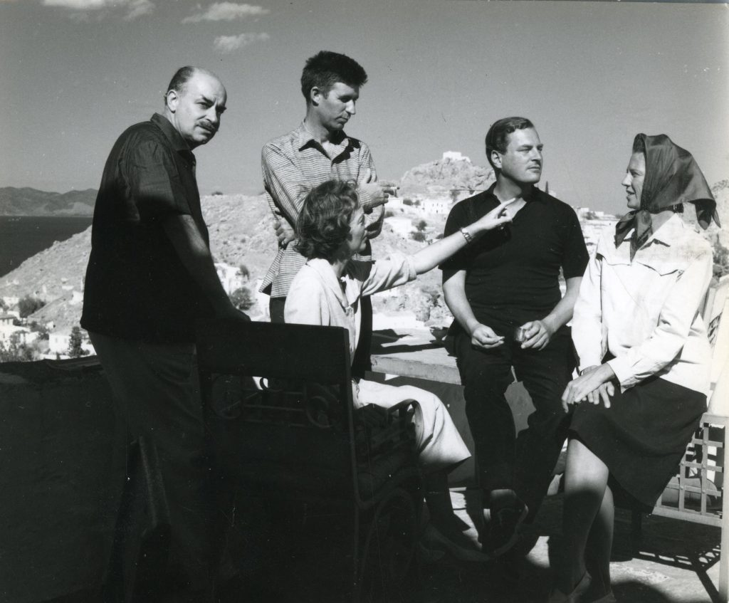 a black and white photo of a group of people on a Greek terrace