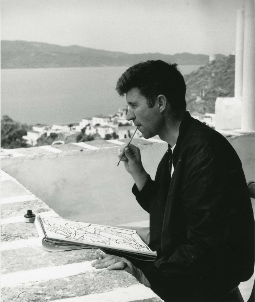 a side profile photo of a man on a Greek balcony with a paint brush