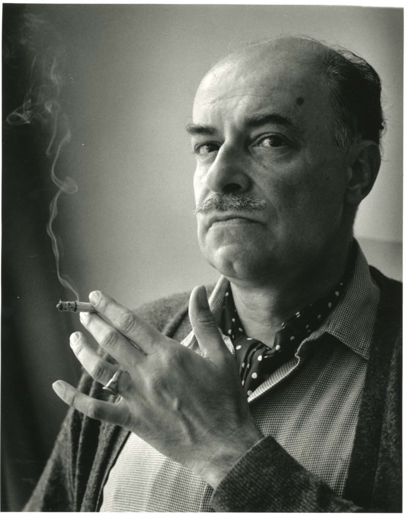 a photo of an enigmatic bald man with a mustache smoking a cigarette