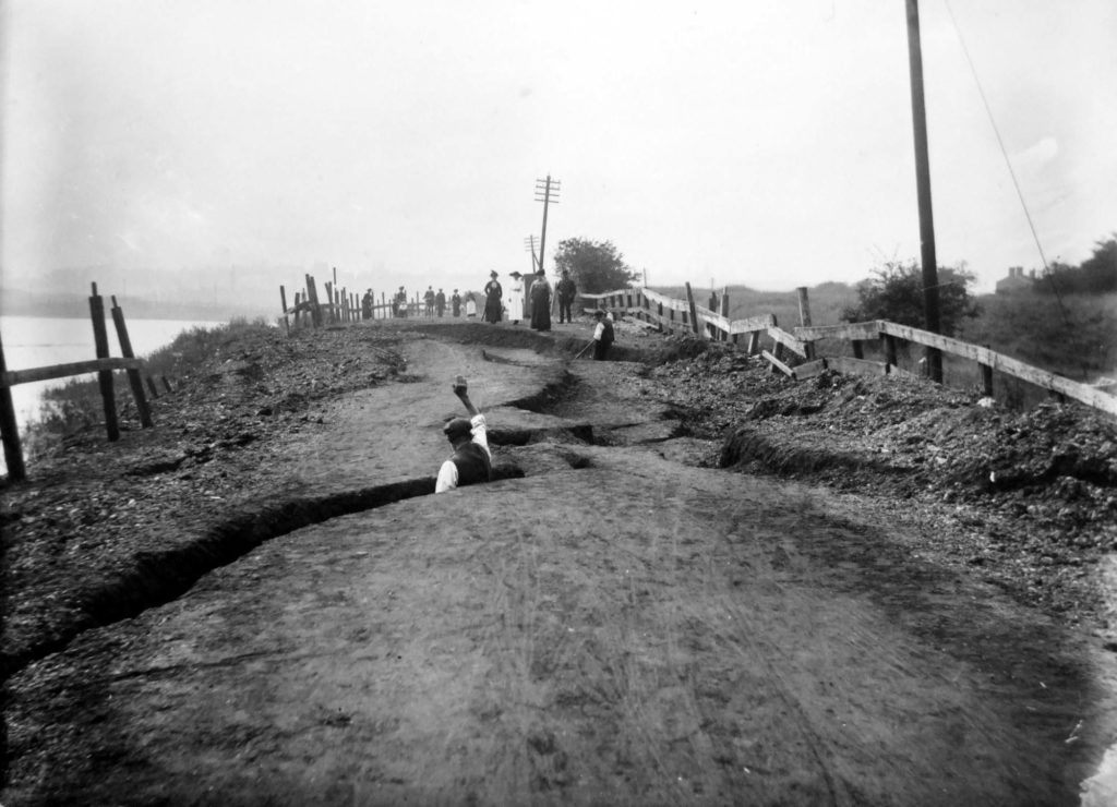 a photo of a man appearing from a revace in a road waving to two women in the distance