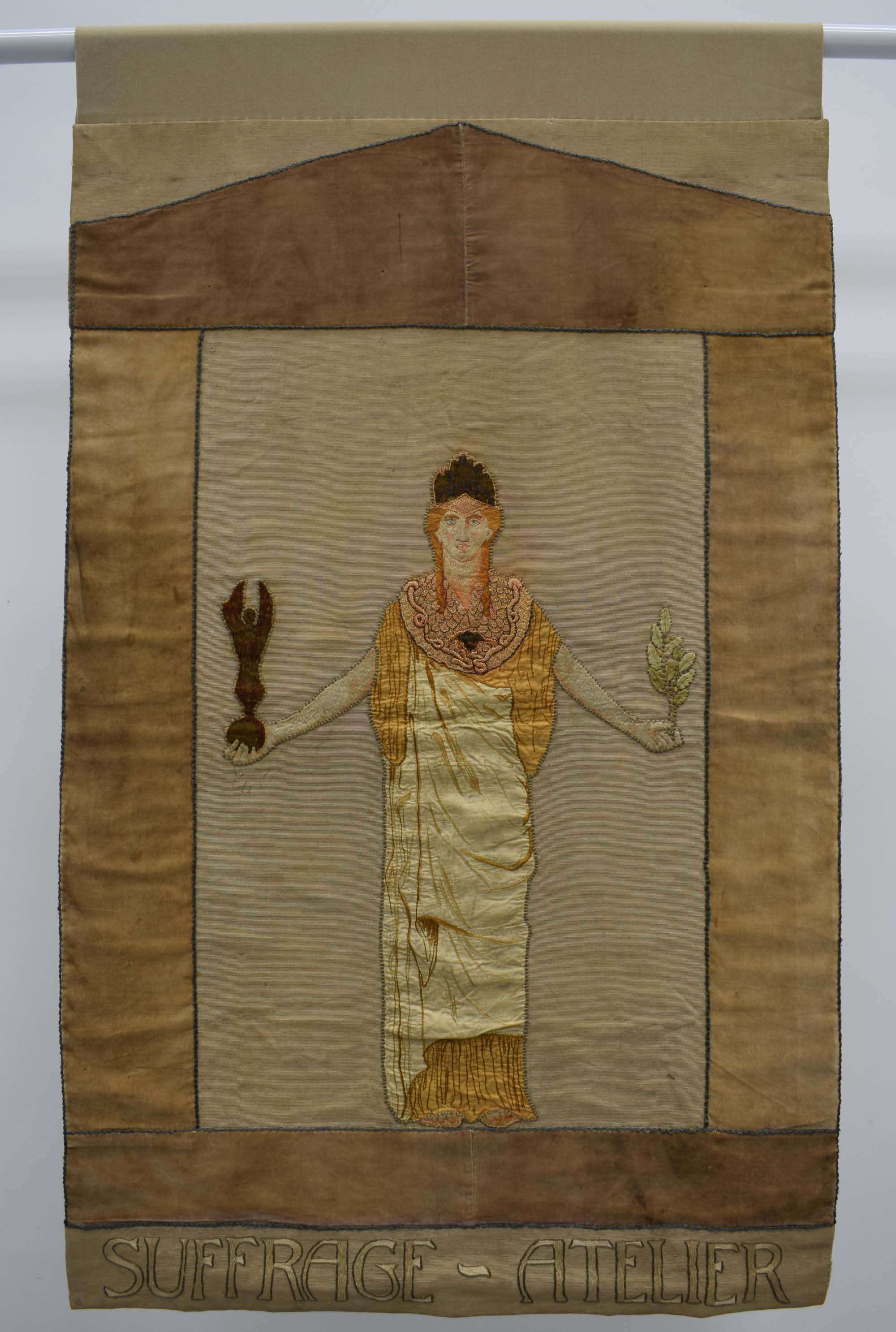 Suffrage Atelier banner iwht a central female art deco style figure holding a torch
