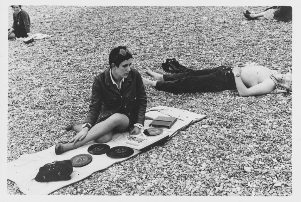 a photo of a mod girl playing 45rpm records on a portable record player on a towel liad out on the pebbles of Brighton beach