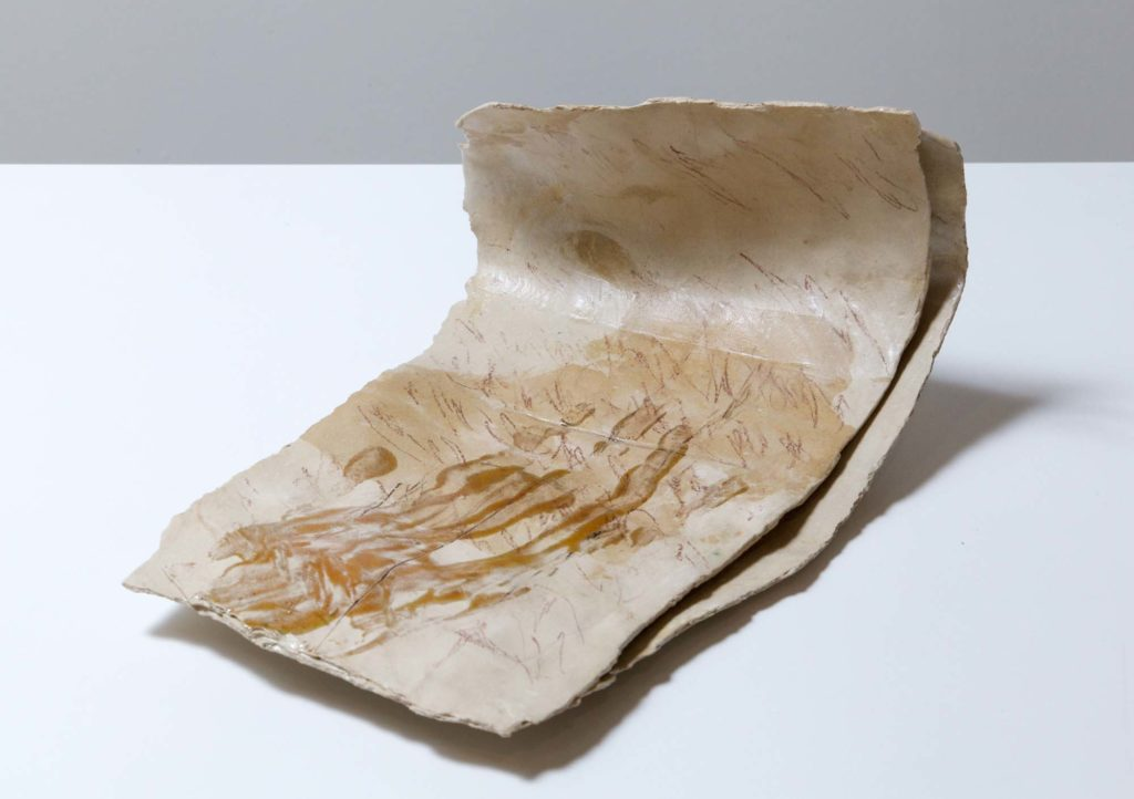 a photo of a folded ceramic sculpture resembling a piece of paper
