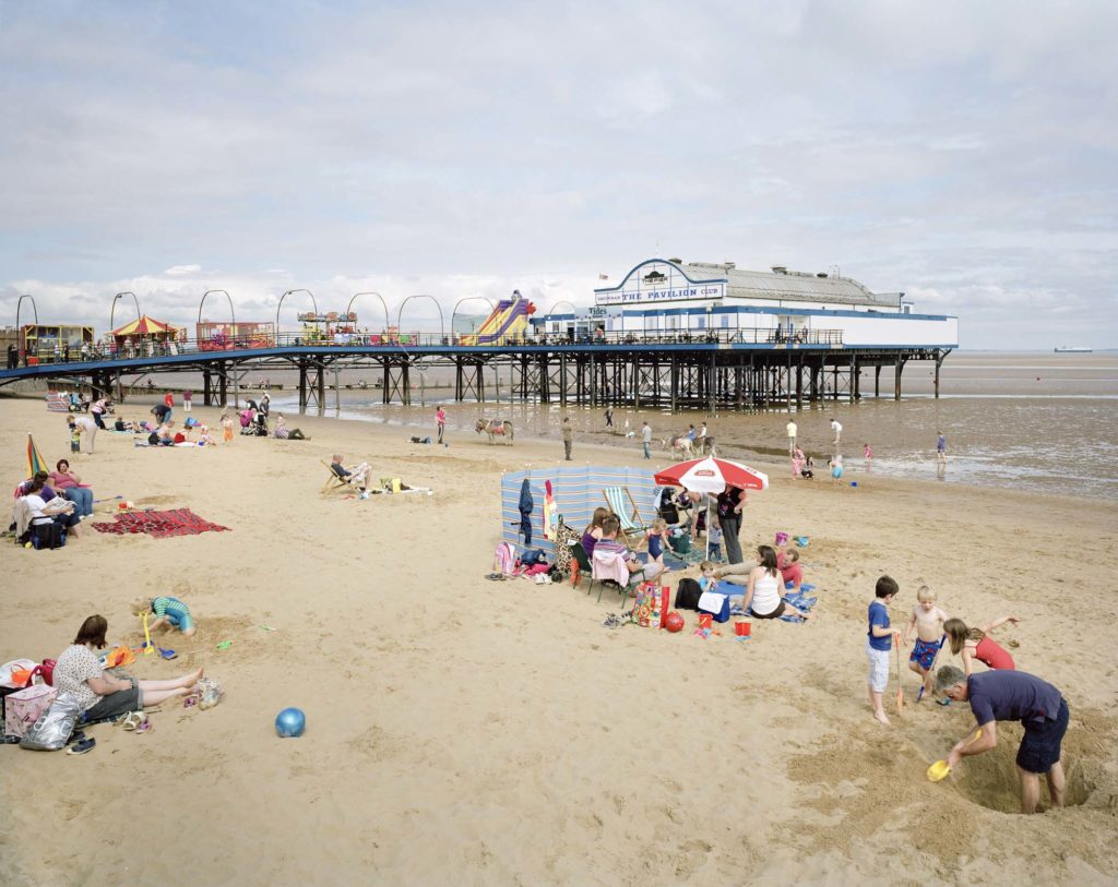 a colour photo of a seaside pier seen from the beach with holidaymakers in the foreground
