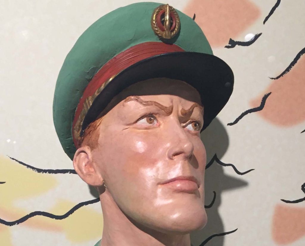 a plaster bust of Dan Dare wearing a green peaked cap