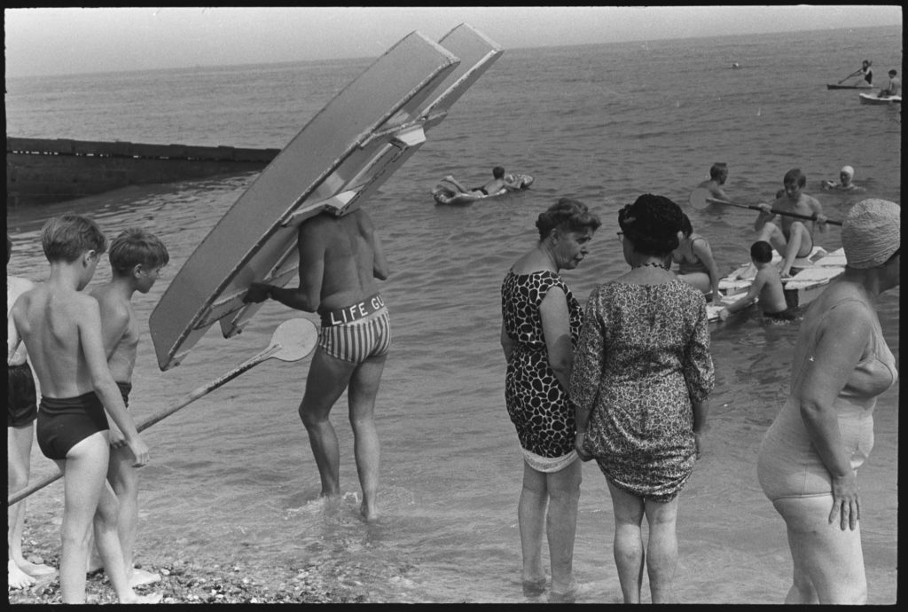 a black and white photo of people on a beach shoreline with a man carrying a small boat on his head
