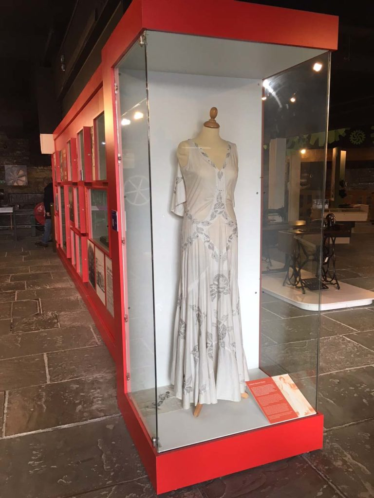 a photo of a long white evening gown in a display case