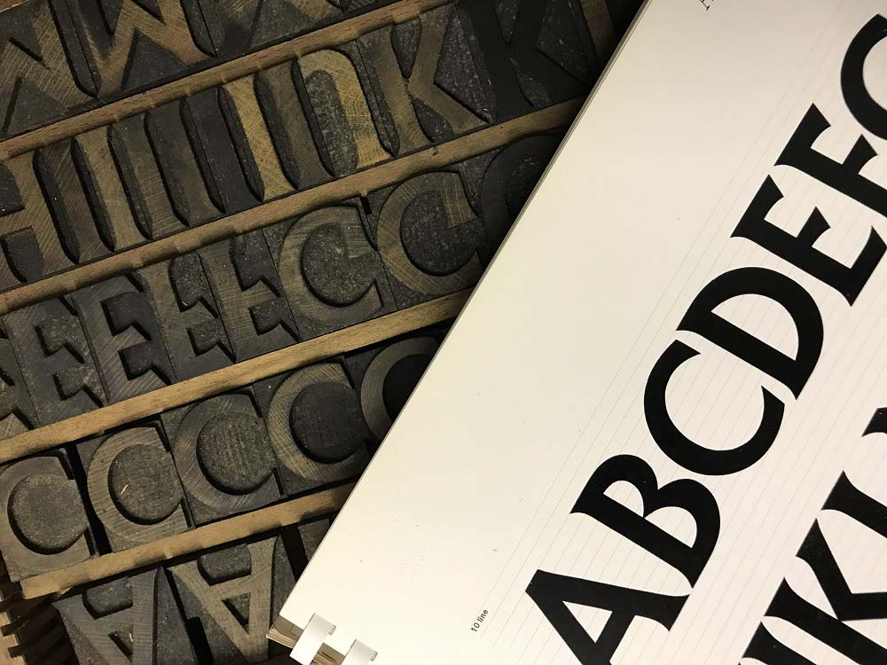 a photo of a letter type blocks in a case and a printed alphabet
