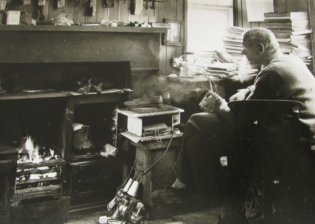 a photo of a man in a office with an open fire and cat asleep above the stove