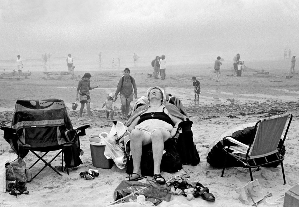 a black and white photo by David Hurn of an elderly lady asleep in her deckchair on a foggy beech