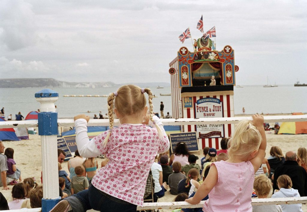 a photo of tow girls watching a Punch and Judy show
