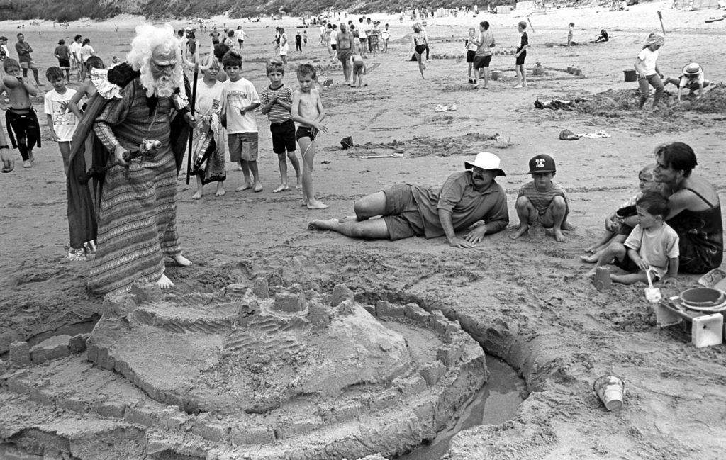 a photo of a family group on a beach next a sandcastle inspected by a man with plastic trident and a rubber mask of an old man