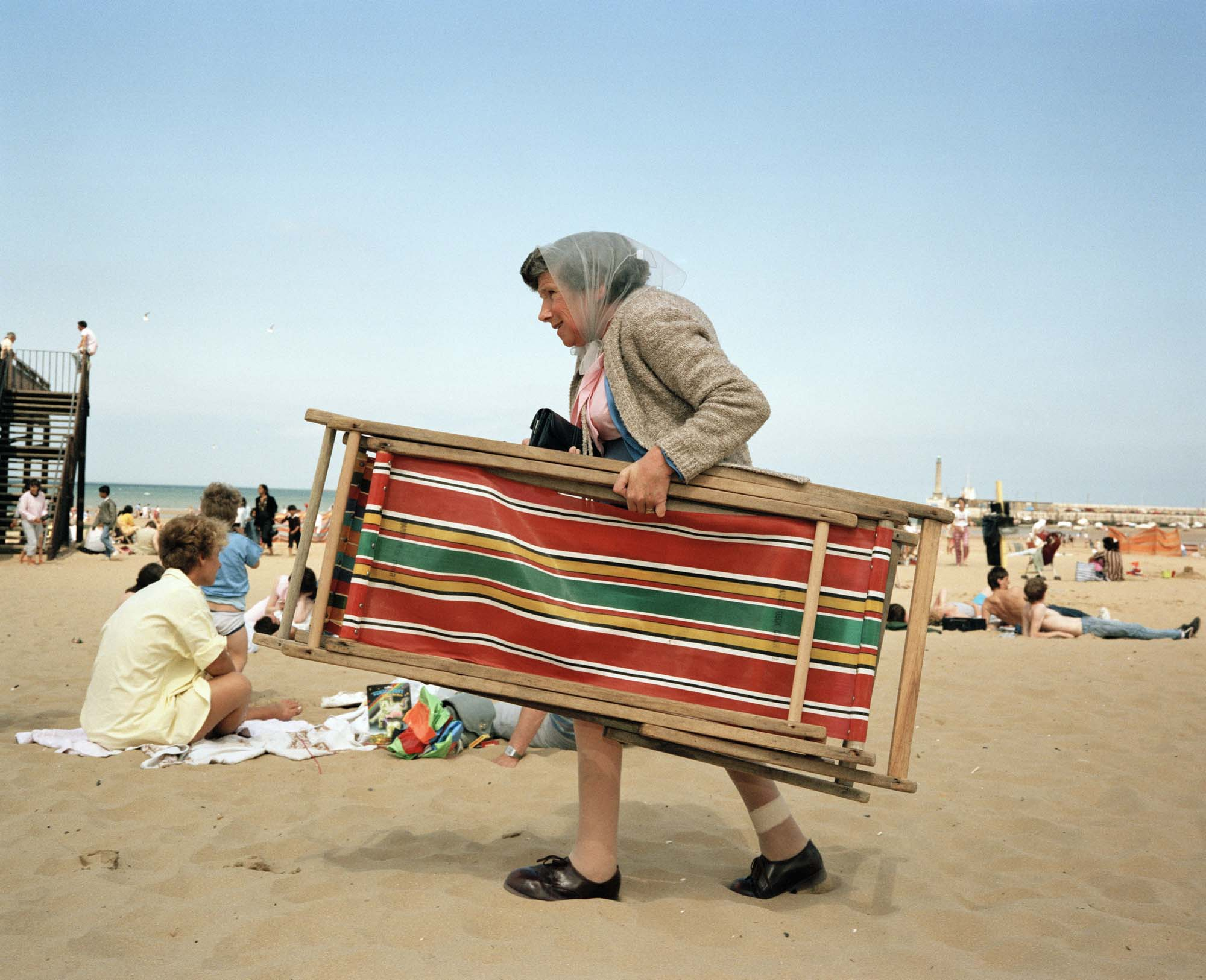 a Martin Parr photograph of an old lady carrying a deck chair across a beach