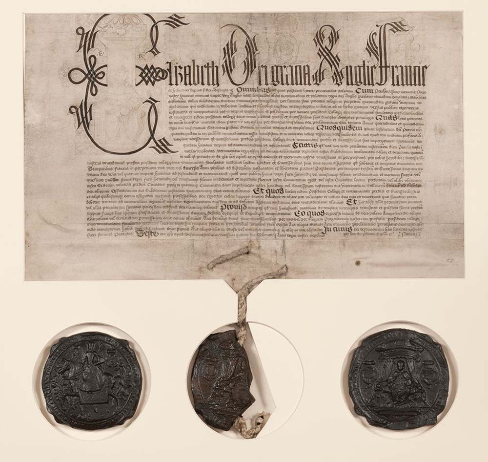 a photo of a latin document with three huge wax seals hanging from it