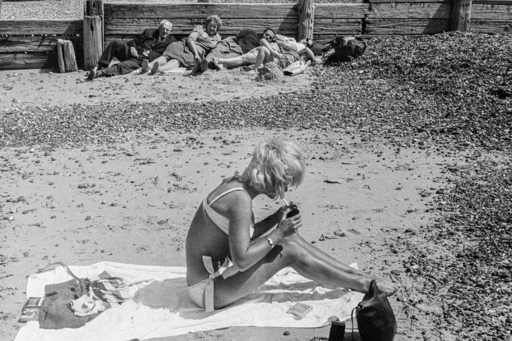 a black and white photo of a young woman in a bikini on a beach lighting a fag watched by a three generation family group leaning against a wooden groin