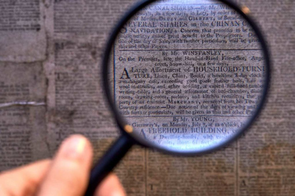 a photo of a magnifying glass over a detail of an eighteenth century newspaper