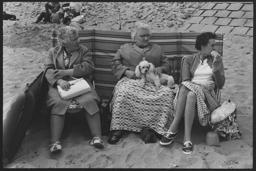 a photo of three ladies two of them elderly sat by a windbreaker on a beach with coats on