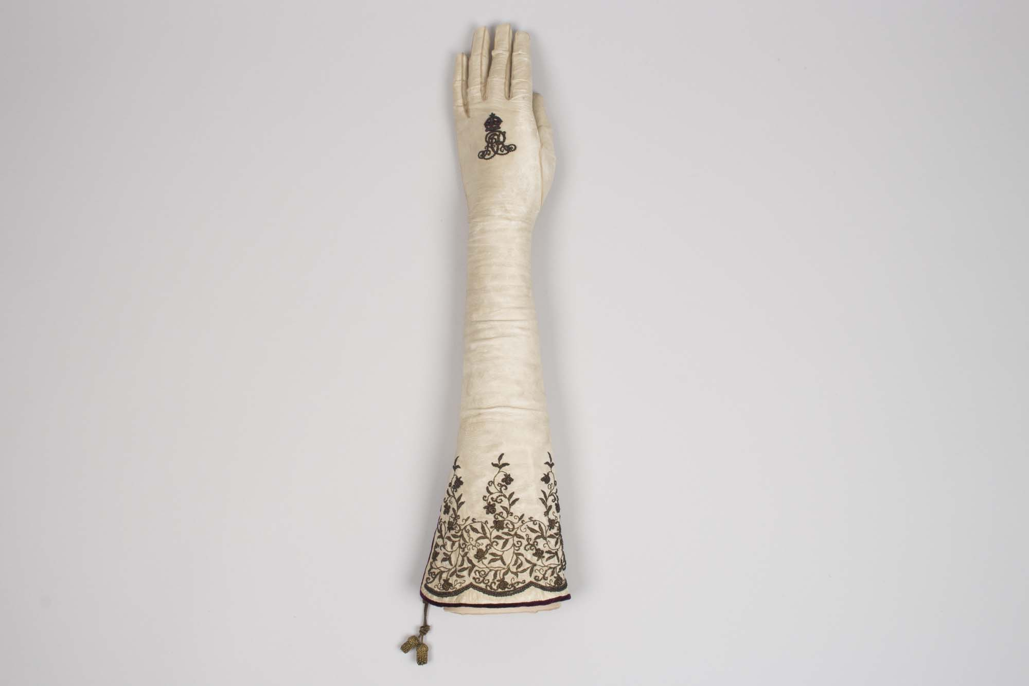 a photo of a long cream glove with a royal cipher on the hand