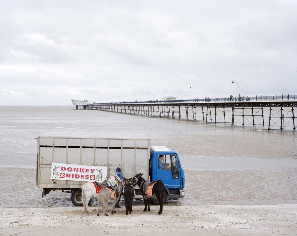 a photo of a seaside pier at Cleethorpes with a lorry and two donkeys on the empty beach in the foreground