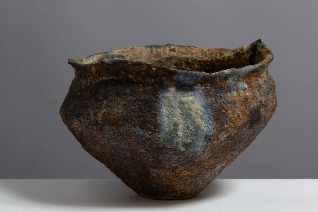 a photo of a textured pot with grey and rust browns and a tactile surface