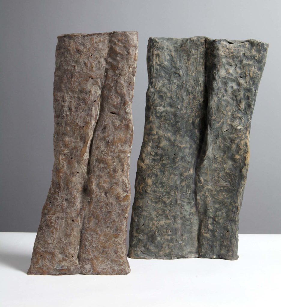 a photo of two ceramic forms by Sara Radstone leaning like standing stones