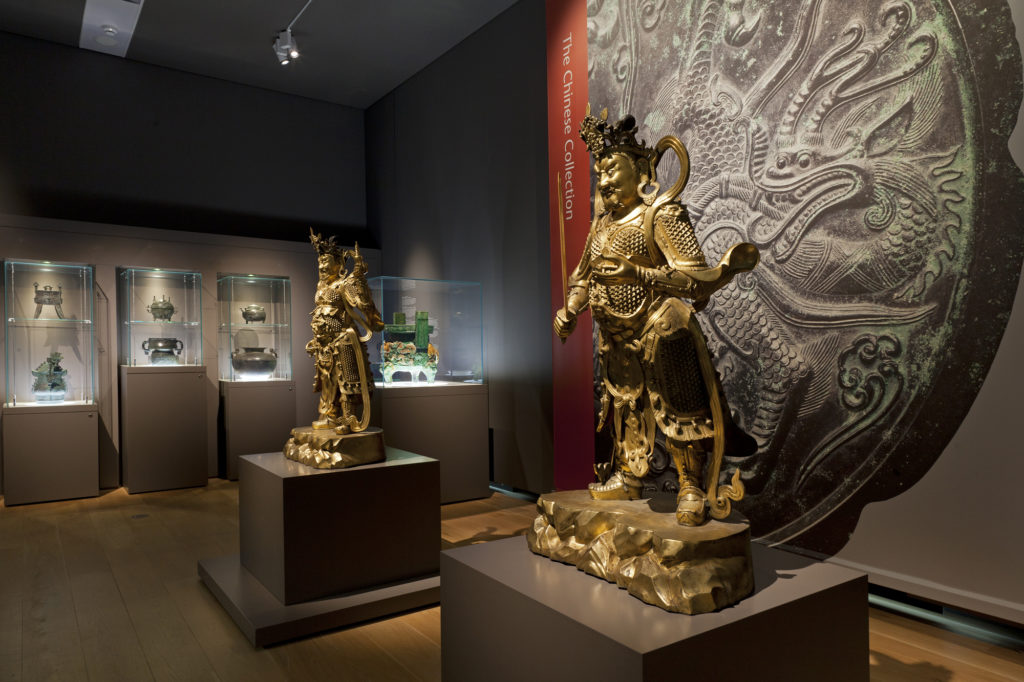 photograph of large bronze Chinese figures in a dark museum gallery