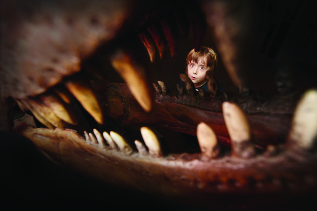 photograph showing child perring through jaws of dinosaur